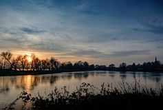 Sunset over a large nature reserve and wetland area seen in winter. The large expanse of water is home to many migrating birds and wildfowl and is in a protected Royalty Free Stock Photo