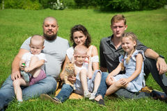 Large family with a cat on the lawn Stock Photos