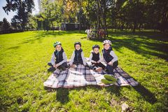 Large family Caucasian children. Three brothers and sister sitting resting on blanket outside the park. Green lawn grass royalty free stock image