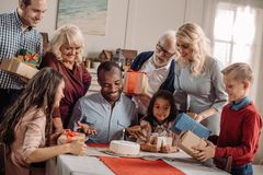 large family presenting cake and gifts to happy african royalty free stock image