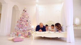 Large family communicates, mother and father with their young sons have fun, lying on large bed in bright bedroom with. Caring parents and twin boys dream stock footage