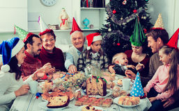 Large family eating together during festive Christmas dinner. Large positive smiling family eating together during festive Christmas dinner Royalty Free Stock Image