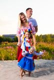 Large family in ethnic Ukrainian costumes sit on the meadow, the concept of a large family. Large family in ethnic Ukrainian costumes sit on the meadow, the stock photo