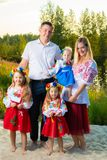 Large family in ethnic Ukrainian costumes sit on the meadow, the concept of a large family. royalty free stock images