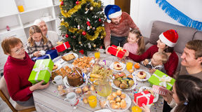 Large family handing gifts to each other Stock Photos