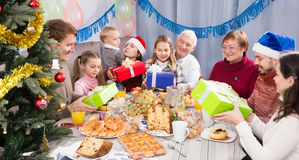 Large family handing gifts to each other. Large family handing the gifts to each other during Christmas dinner royalty free stock images