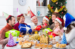 Large family handing gifts to each other. Large family handing a gifts to each other during a Christmas dinner stock photography
