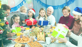 Large family handing gifts to each other. During the Christmas dinner stock photography