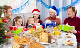 Large family handing gifts to each other. During Christmas dinner stock photography
