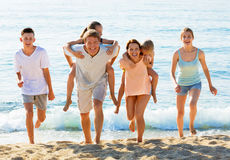 Large family happily running and carrying kids on parents back Royalty Free Stock Photos