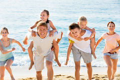 Large family happily running and carrying kids on parents back Stock Image