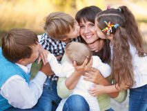Large family hugging and having fun outdoors. Selective focus on mother's hands and the head of the baby. Son and daughter kissing mother. Happy family concept royalty free stock image