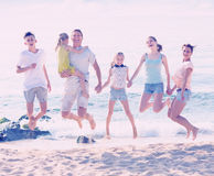 Large family jumping on sandy beach Royalty Free Stock Photography