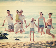 Large family jumping up together on beach on clear summer day Stock Image