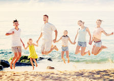 Large family jumping up together on beach on clear summer day Royalty Free Stock Photos