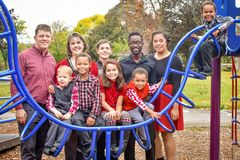Large Family at Park. A large family with two parents and eight children, some biological and some adopted, multi racial children at a park playing bars royalty free stock photos