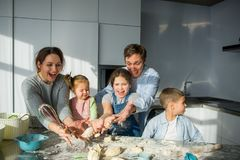 Large family prepares something of dough. Parents and three children at the kitchen table. Merry and useful pastime Royalty Free Stock Images