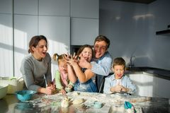 Large family prepares something of dough. Parents and three children at the kitchen table. Merry and useful pastime Stock Image