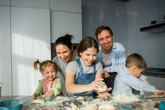 Large family prepares something of dough. Parents and three children at the kitchen table. Merry and useful pastime Stock Photography