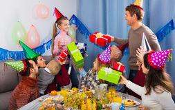 Large family presenting gifts to girl during birthday party Stock Images