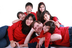 Large family of seven. In red shirts and jeans isolated on white Royalty Free Stock Photo