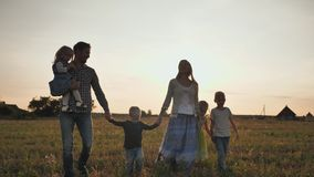 A large family of six people walk on the floor at sunset. stock footage
