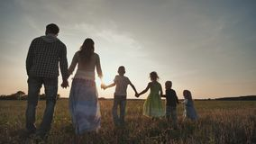 A large family of six people walk on the floor at sunset. stock video