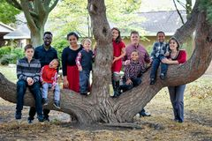 Large Family by Tree. A large family with two parents and eight children, some biological and some adopted, multi racial children by a cool tree stock images