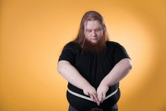 A large fat man measures his large sizes with a ribbon. stock images