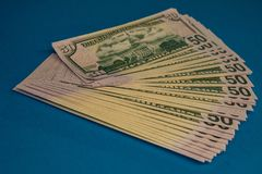 Large Fat Money Roll  on a blue Background royalty free stock photos