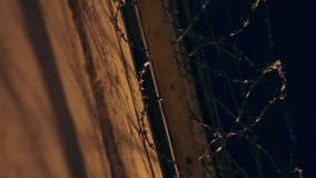 Large fence with barbed wire in the night stock video footage