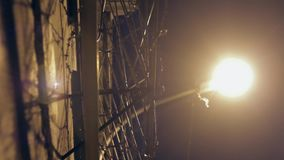 Large fence with barbed wire at night lit by a lantern stock footage