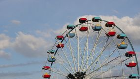 Large ferris wheel with open cabins quickly turns against a blue sky.  stock footage