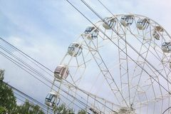 Large ferris wheel is spinning in an amusement park. Stock Image