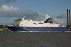 Large ferry on a sea crossing. Blue and white ferry sailing under a dramatic sky Stock Photo