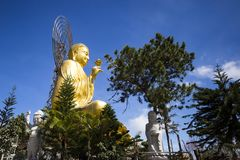 A large figure of a seated golden buddha. A large, majestic and beautiful figure of a seated golden buddha in Dalat, Vietnam on the blue cloudy sky background Royalty Free Stock Image