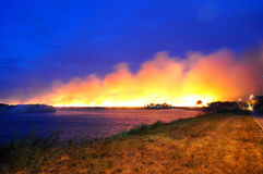 A large fire in a field near the water Royalty Free Stock Photography