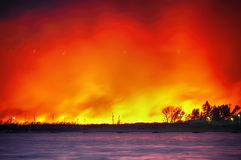 A large fire in a field near the water Royalty Free Stock Image