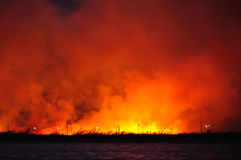 A large fire in a field near the water Stock Photos