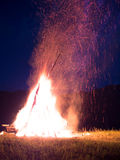 Large fire with sparks lit in the middle of the field Royalty Free Stock Photos