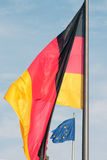 Large flag of Germany in front of small flag of European Union Royalty Free Stock Photos