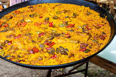 Large flat frying pan with cooked homemade Spanish paella with variety of meats, vegetables, rice, tomato sauce, spices Stock Images