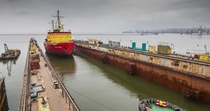Large floating dock rises above the water surface for repair. In Azov sea with help of tugboat stock video