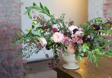 Large Floral Arrangement in Urn. Pink, blush and purple Aubergine colored flowers and greenery in a large ceremony arrangement Royalty Free Stock Photo