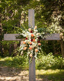 Large flower arrangement hanging on an old wooden cross outside Stock Photo