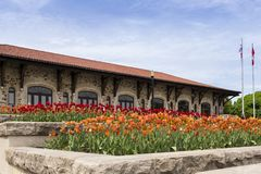 Large flowerbeds of orange and red tulips with the Mount-Royal Chalet in the background. During a sunny spring day, Montreal, Quebec, Canada stock photos