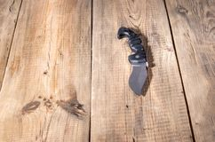 Large folding knife on a wooden background. A massive knife on the table. Front royalty free stock photography