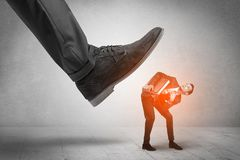 Large foot stepping down small man. Large formal shoe stepping down young small entrant man Stock Photo