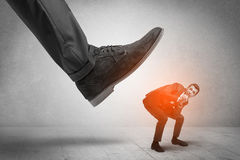 Large foot stepping down small man Royalty Free Stock Image
