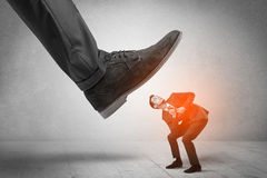 Large foot stepping down small man Stock Images